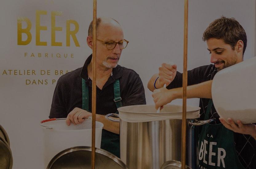 Père et fils qui brassent de la bière artisanale dans un atelier de brassage parisien