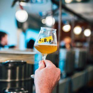 Verre LBF rempli de bière blonde, avec en fond l'atelier de brassage